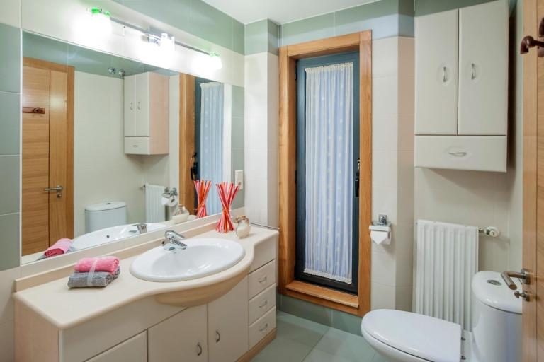 Cuarto de baño con un gran mueble y espejo