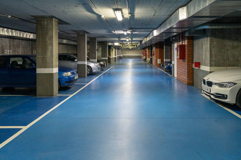 Vía de circulación garaje en bajo de Costa Dulce Sada_ Suelo azul_ paredes de hormigón y ladrillo visto