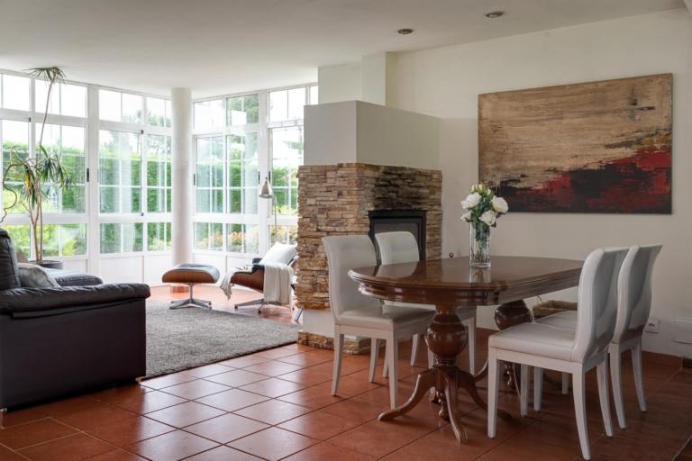 Salón comedor con mesa y sillas, sofá y chimenea de piedra