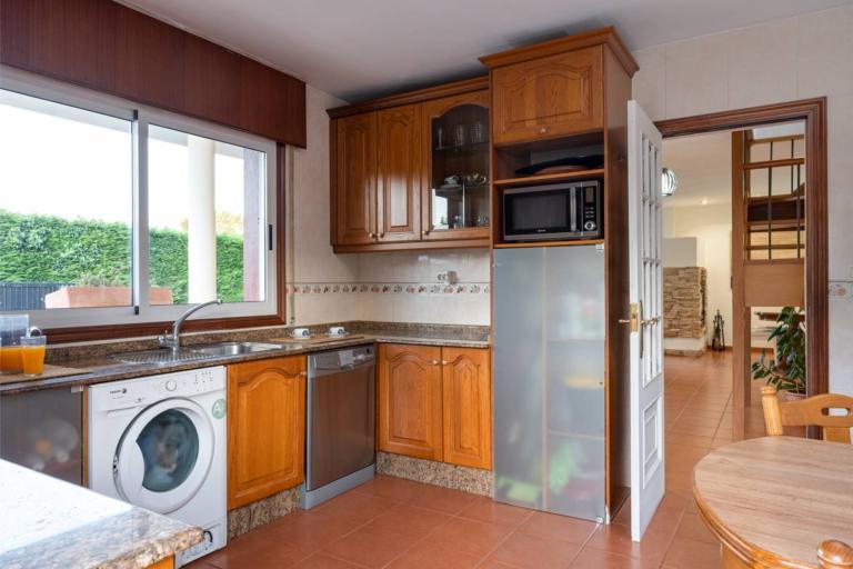 Cocina con muebles rústicos y electrodomésticos