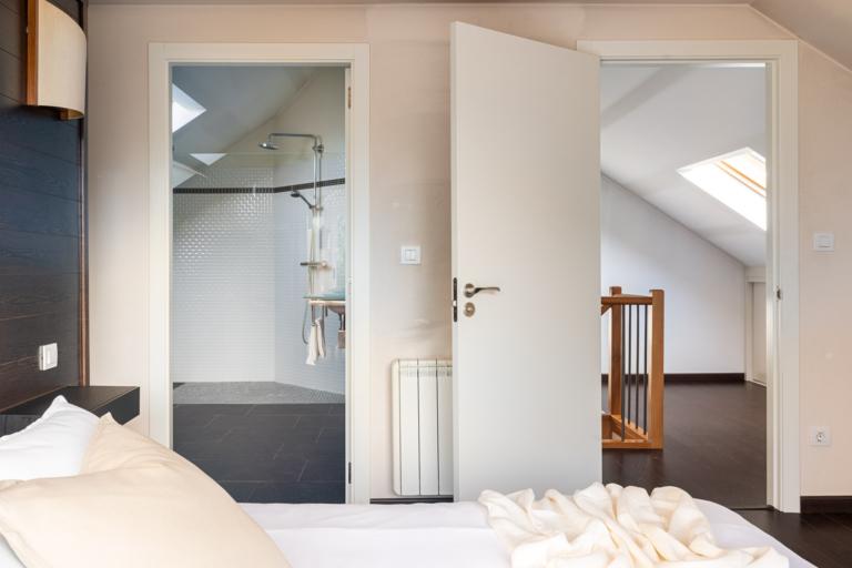 Detalle de la cama del dormitorio principal y acceso al baño