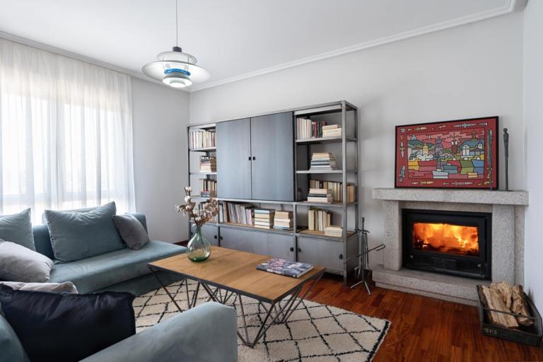 Salón con sofás y librería, con chimenea de granito
