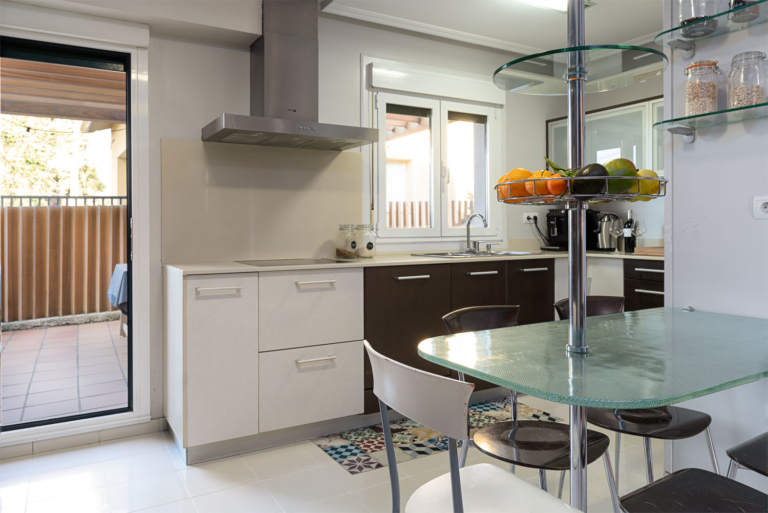 Cocina de diseño lacada en blanco y negro y acceso directo a la terraza