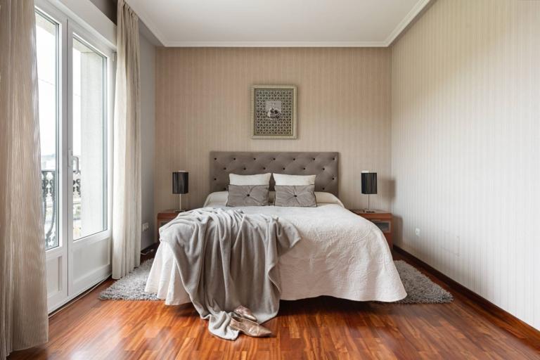 Cama y mesitas de noche en dormitorio con terraza
