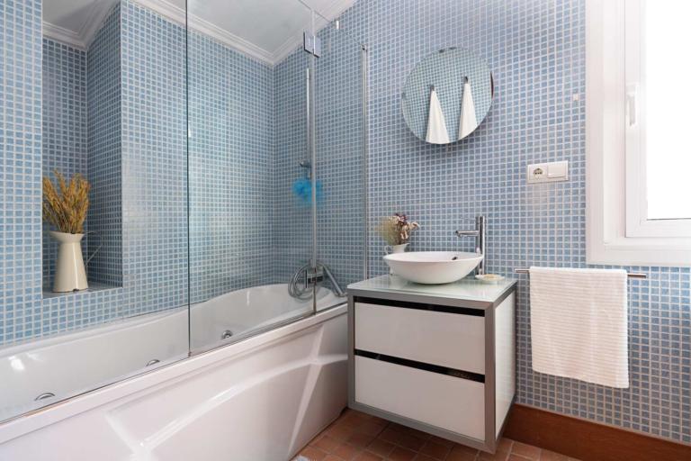 Cuarto de baño con bañera hidromasaje y lavabo de diseño minimalista