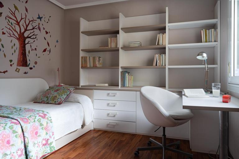 Estudio con sofá cama y librería con mesa de trabajo de color blanco
