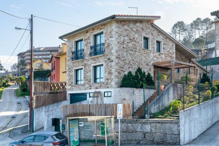 Fachada lateral y jardín de casa de piedra