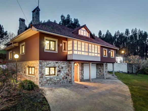 Fotografía nocturna de fachada principal de vivienda unifamiliar con porche y galería superior_Acceso a parcela.