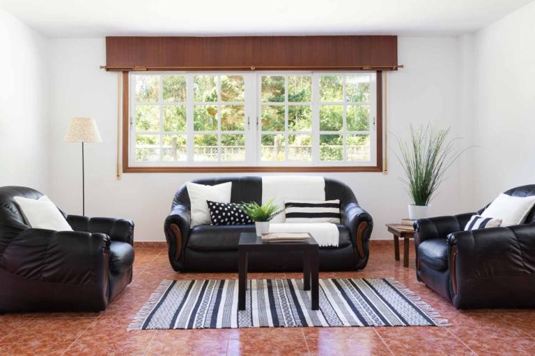 Conjunto de sofás en cuero negro y vistas al jardín desde el salón