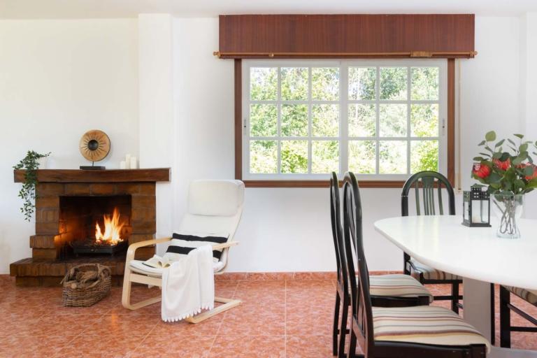 Detalle de mesa de comedor y chimena encendida con vistas al jardín