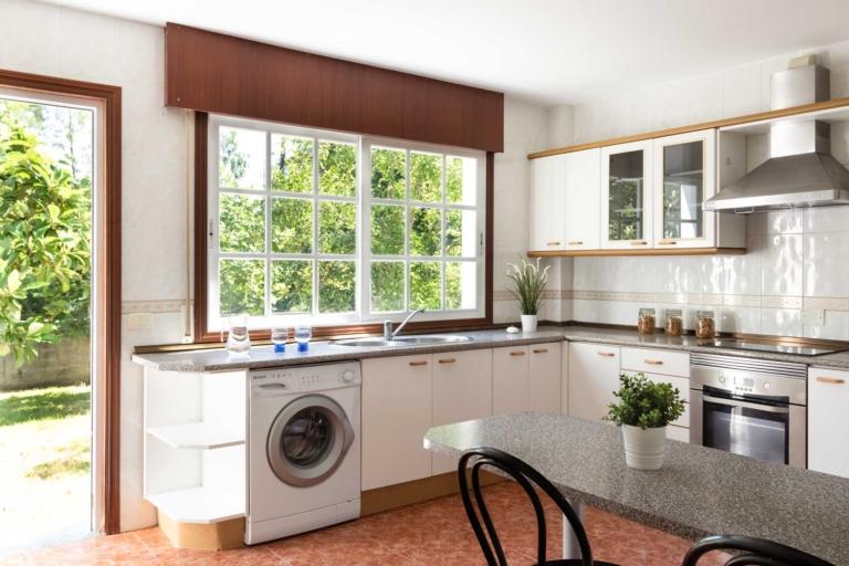 Cocina con muebles en blanco y puerta de acceso directo al jardín