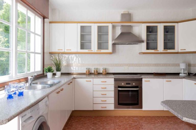 Cocina con encimera de granito, muebles en blanco y electrodomésticos