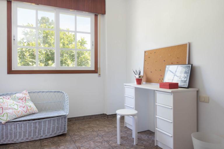 Mesa de estudio y sofá de mimbre en habitación de la primera planta