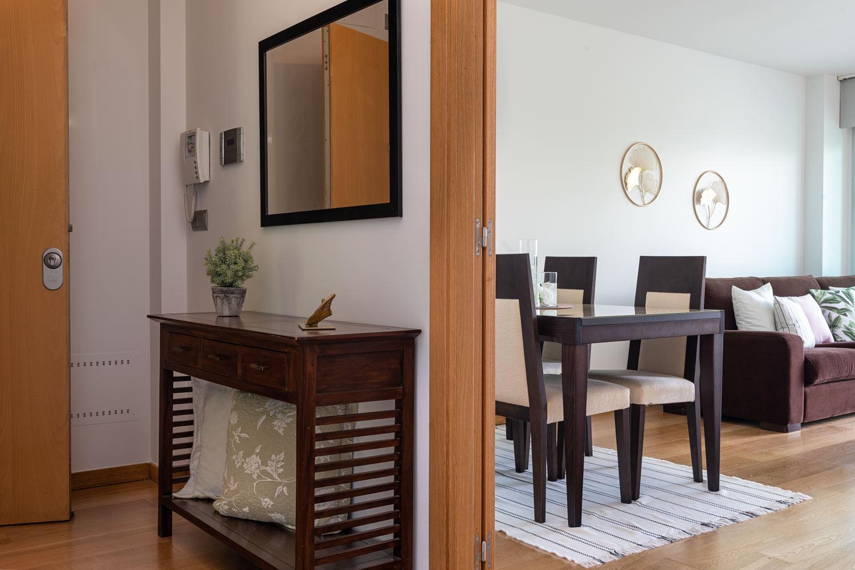 Recibidor de bajo en Costa Dulce Sada_ mueble bajo con decoración y y un espejo encima. A través de una puerta doble en roble, vemos el salón comedor