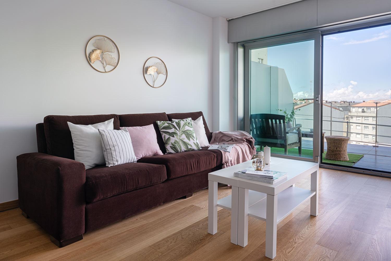 Salón+terraza bajo Costa Dulce_vistas_ Detalle del sofá marrón y la mesa blanca con decoración sencilla. Textiles claros para dar luminosidad