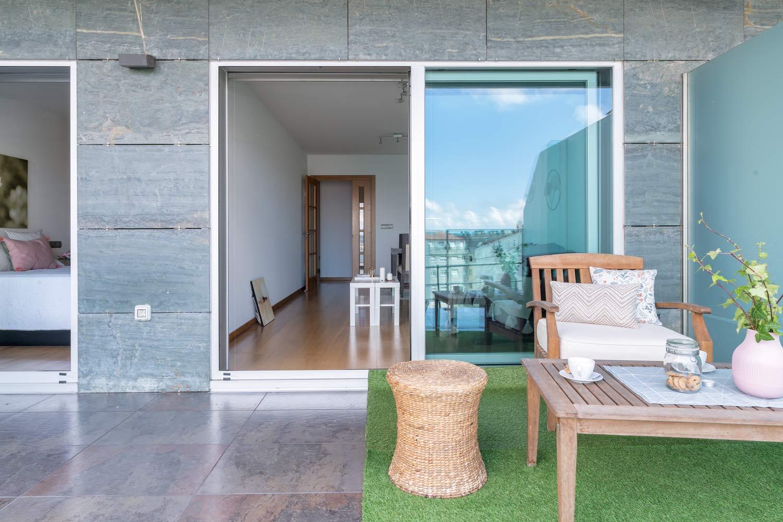 Fotografía de terraza en bajo Costa Dulce_césped artificial y mobiliario de jardín preaparado con home staging_acceso a dormitorio y salón comedor