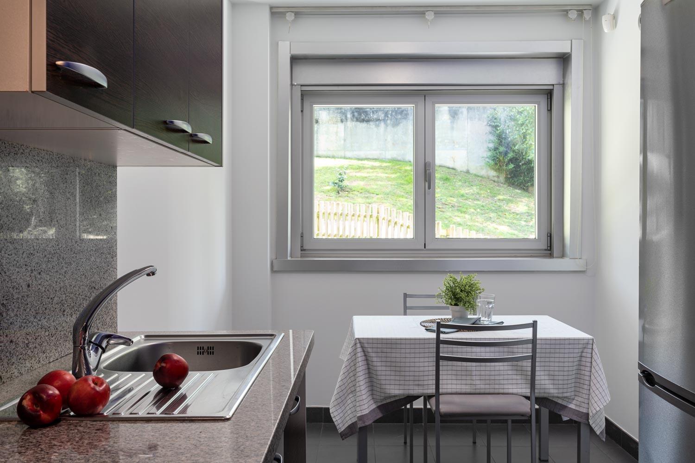 Detalle de cocina en bajo Costa Dulce. Líneas Rectas y puertas en madera oscura con encimera en Granito gris_ Zona fregadero y comedor preparada con Home Staging
