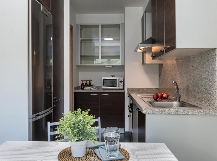 Cocina en bajo Costa Dulce. Líneas Rectas, electrodomésticos integrados y puertas en madera oscura con encimera en Granito gris_ Preparación con Home Staging