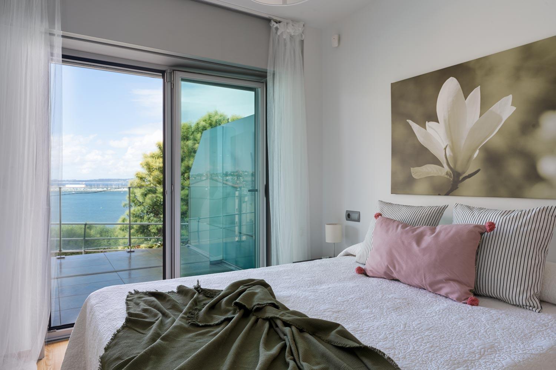 Dormitorio principal en bajo Costa Dulce Sada cojín rosa y manta verde_ventanal con puerta abatible y vistas al mar
