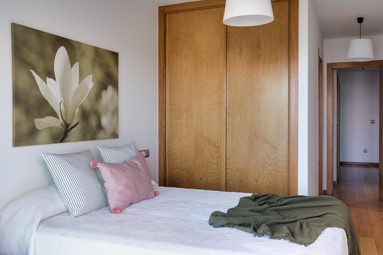 Dormitorio principal en bajo Costa Dulce Sada cojín rosa y manta verde_acceso y armario empotrado