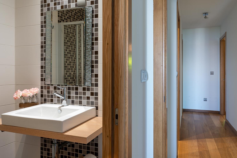 Baño en suite habitación principal en bajo Costa Dulce Sada_ encimera de madera y lavabo blanco con flores en tarros de cristal