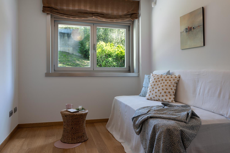 Dormitoirio individual en bajo Costa Dulce Sada_ cojjines verdes y blanco con puntos ocre_mesita de ratán_ventana