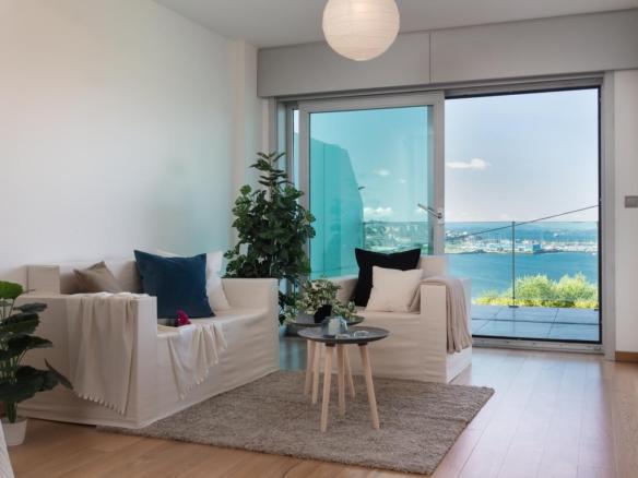 Salón con sofás y acceso a la terraza con vistas al mar