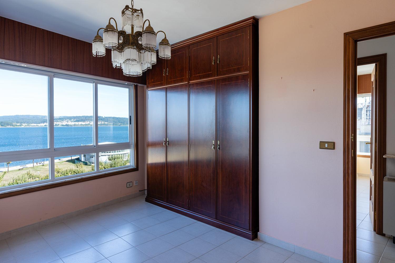 Dormitorio vacío con armario y vista panorámica hacia el mar