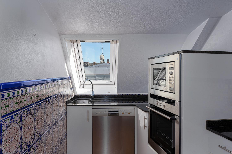 Cocina abuhardillada dúplex con velux y azulejos de inspiración mediterránea_ electrodomésticos en acero inoxidable