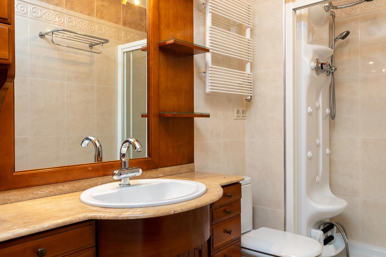 Cuarto de baño principal con mueble clásico de madera en dúplex_ hidromasaje y toallero eléctrico