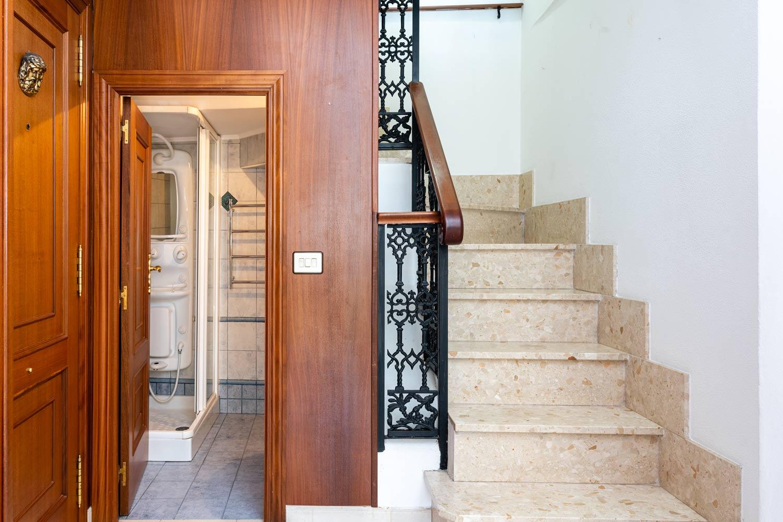 Entrada con baño bajo escaleras dúplex_ panelado de madera_forja en los pasamanos