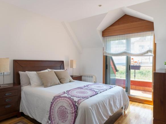 Dormitorio principal abuhardillado con salida a terraza_colores neutros y madera oscura de lineas puras