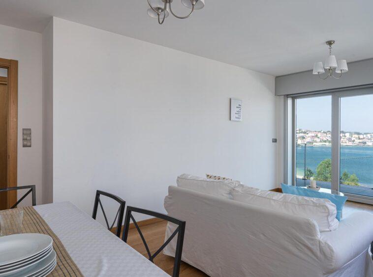 Mesa de comedor y sofá en salón con vistas al mar