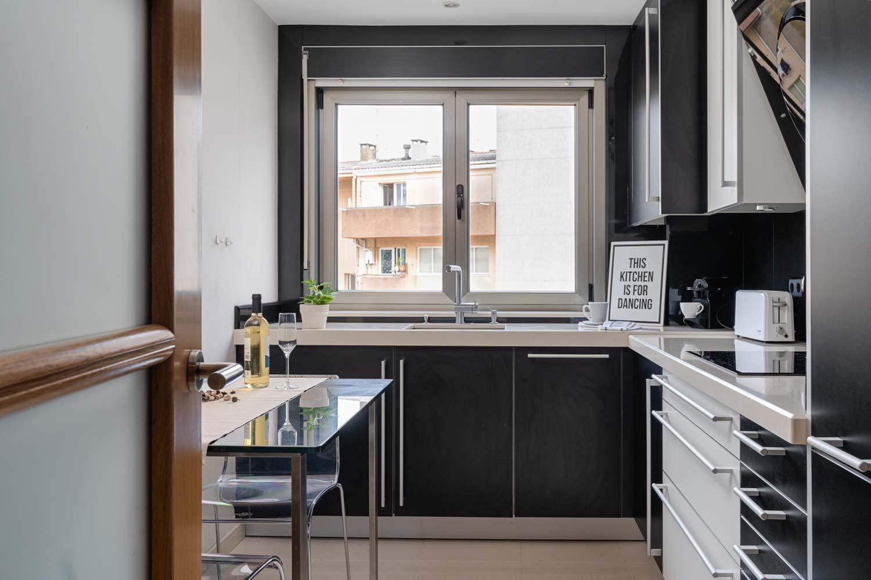 Cocina negra moderna de Santos en piso Rúa Bergondo_fregadero frente a la ventana_ Copas y vino en la mesa