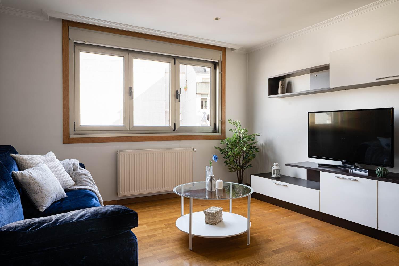 Salón en Rúa Betanzos_ sofá de terciopelo azul y mueble tv