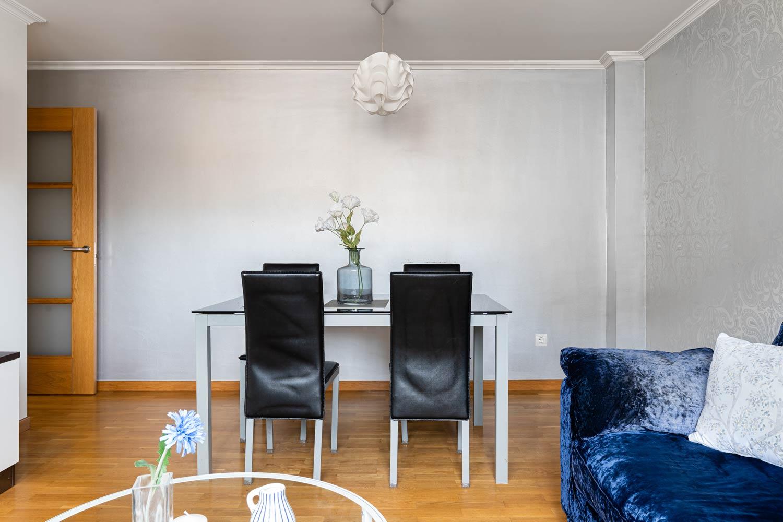 Salón comedor pared plata y sofá de terciopelo azul en Rúa Betanzos_Flores en jarrón sobre la mesa de comedor
