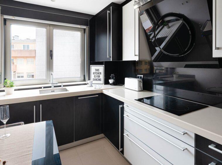 Cocina negra moderna de Santos en piso Rúa Bergondo_vista general en escorzo hacia la ventana