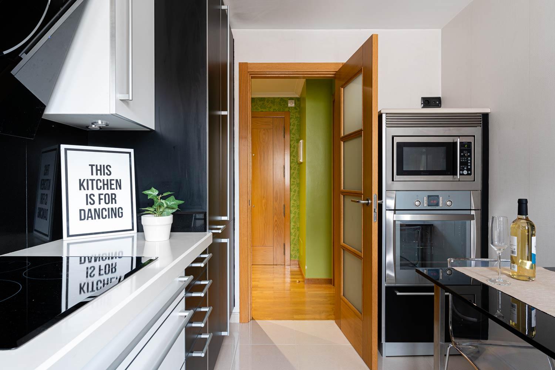 """Cocina negra moderna de Santos en piso Rúa Bergondo_Vista hacia el recibidor_ Cuadro """"This kitchen is for dancing"""" y planta sobre encimera_En la parte derecha hay una columna de horno y microondas"""