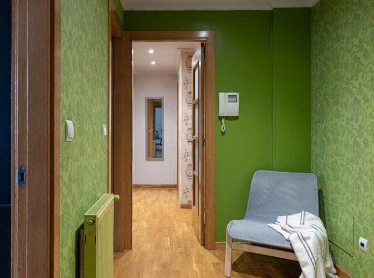 Recibidor en piso Rúa Betanzos_pintura y papel pintado verdes + silla_ Al fondo, el pasillo de las habitaciones y un espejo