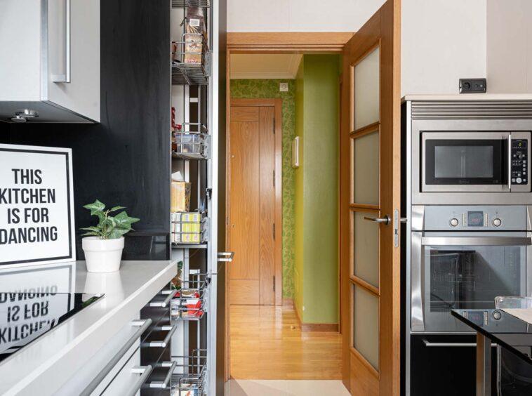 """Cocina negra moderna de Santos en piso Rúa Bergondo_Vista hacia el recibidor_ Cuadro """"This kitchen is for dancing"""" y planta sobre encimera_Alacena vertical extraíble"""