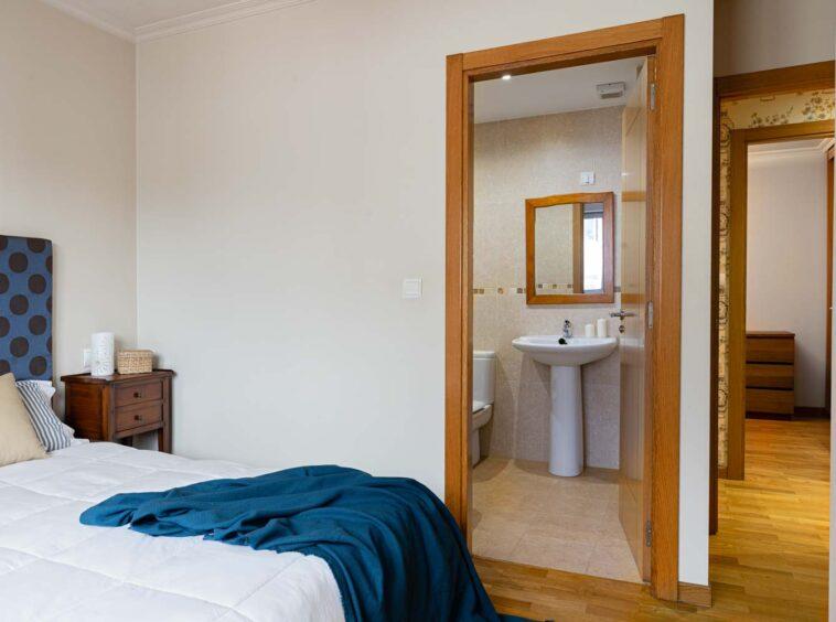 Vista desde el dormitorio principal de piso en Rúa Betanzos_ Manta sobre la cama + baño en suite + pasillo y dormitorio
