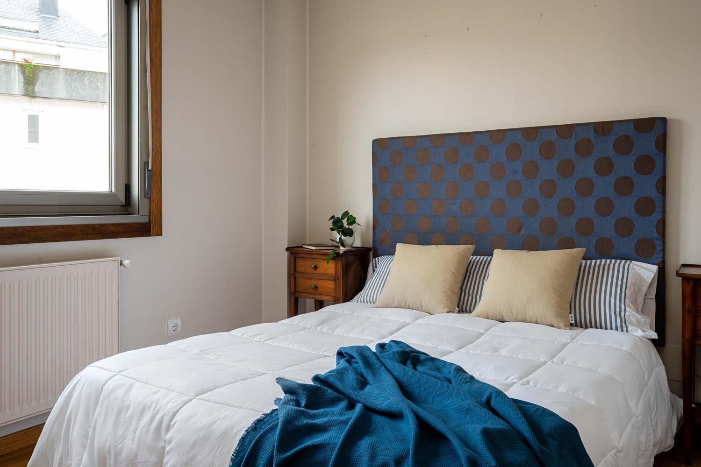 Dormitorio principal en piso Rúa Betanzos_cama con cabecero azul de topos marrones