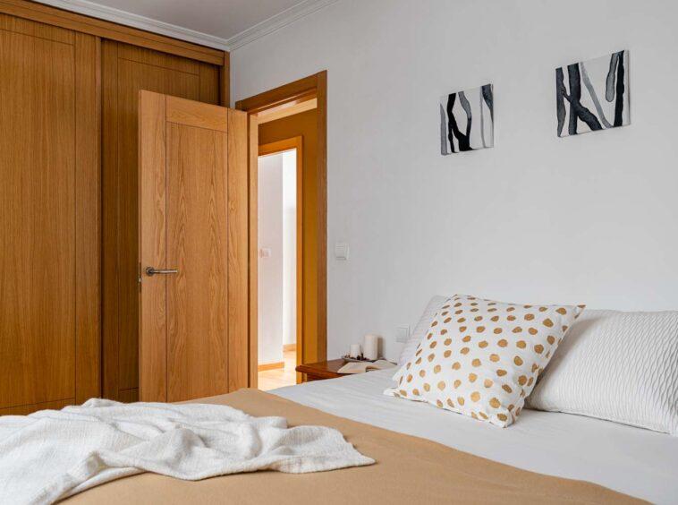 Segundo dormitorio matrimonio con armario empotrado en piso Rúa Betanzos_ textiles blancos y marrones + velas + libro + cuadros abstractos sobre la cama