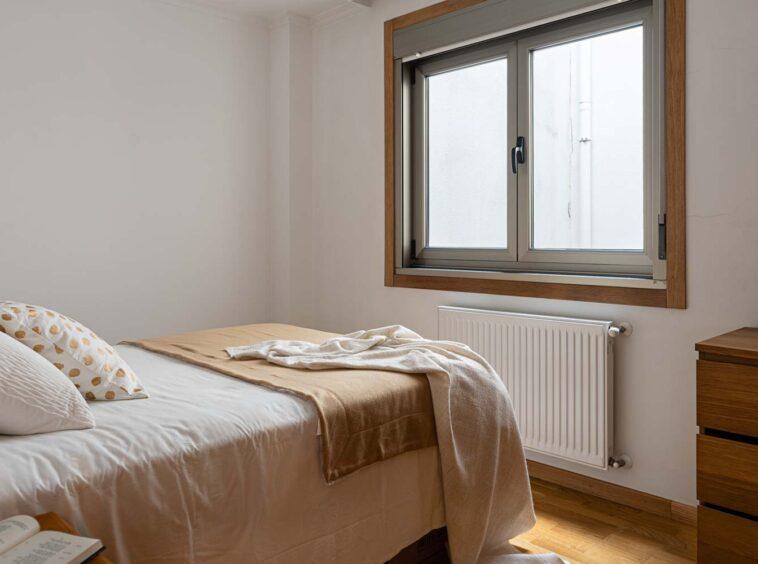 Segundo dormitorio matrimonio hacia patio interior en piso Rúa Betanzos_ textiles blancos y marrones