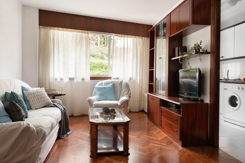 Detalle del salón, con mueble y conjunto de sofás