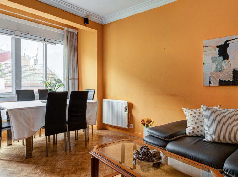Salón con sofá de cuero negro y mesa de comedor con seis sillas